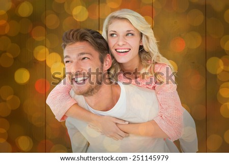 Handsome man giving piggy back to his girlfriend against close up of christmas lights - stock photo