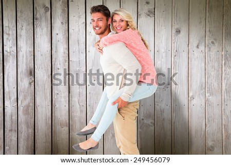 Handsome man giving piggy back to his girlfriend against digitally generated grey wooden planks - stock photo