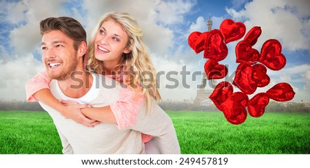 Handsome man giving piggy back to his girlfriend against eiffel tower - stock photo