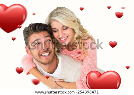 Handsome man giving piggy back to his girlfriend against hearts - stock photo