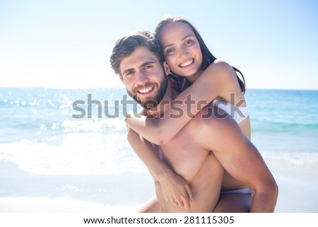 Handsome man giving piggy back to his girlfriend at the beach - stock photo