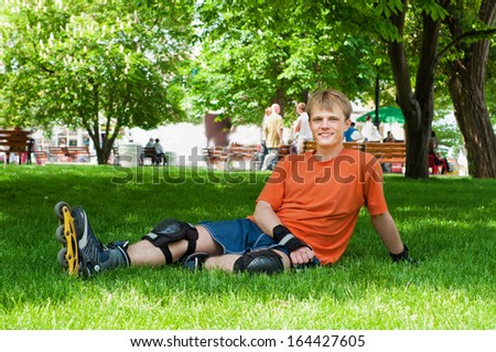 Handsome man going rollerskating in city park - stock photo