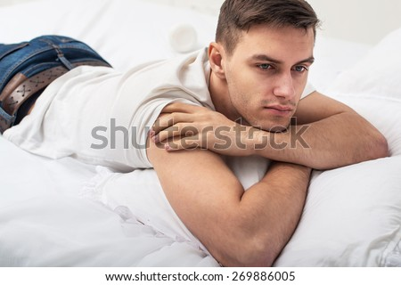 Handsome man guy in white T-shirt and blue jeans lying on a bed - stock photo