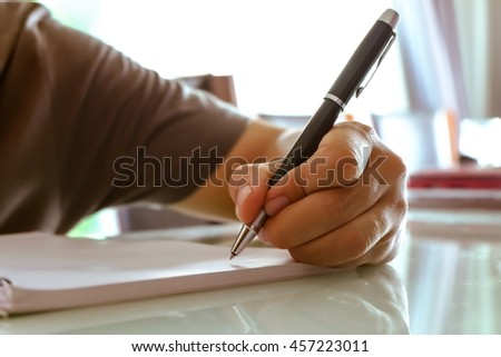 Handsome man hand with pen writing notebook