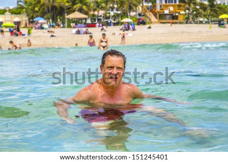 handsome man has fun swimming in the ocean