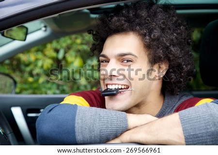 Handsome man having fun with key of new car - stock photo