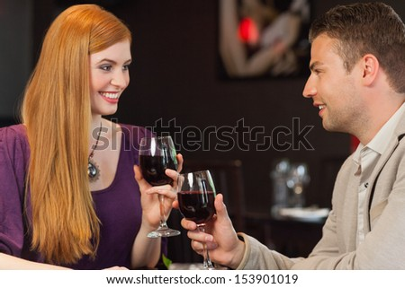 Handsome man having glass of wine with his gorgeous girlfriend in a classy restaurant - stock photo