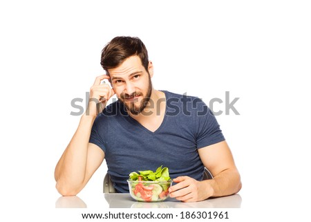 Handsome man having in front healthy food and junk food, choosing salad - stock photo