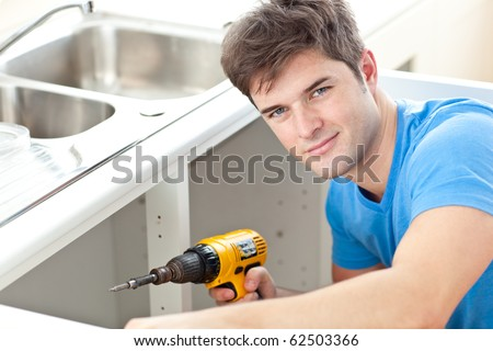 Handsome man holding a drill repairing a kitchen sink at home - stock photo