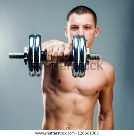 handsome man holding a dumbbell in front on a gray background - stock photo