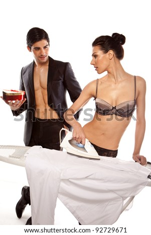 Handsome man holding a gift and standing watching a beautiful woman in lingerie ironing his shirt