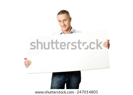 Handsome man holding an empty banner. - stock photo