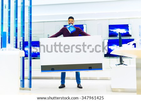 Handsome man holding big unpacked TV at TV shop. He is buying a new big TV. Empty space for your text. Shallow depth of field. - stock photo