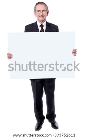 Handsome man holding blank white billboard. Showing to camera - stock photo