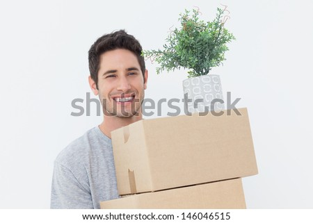Handsome man holding boxes because he is moving - stock photo