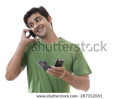 Handsome man holding cell phones while on call