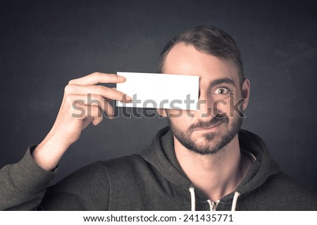 Handsome man holding copy space paper at his eye concept - stock photo