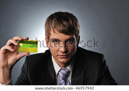 Handsome man holding credit card - stock photo