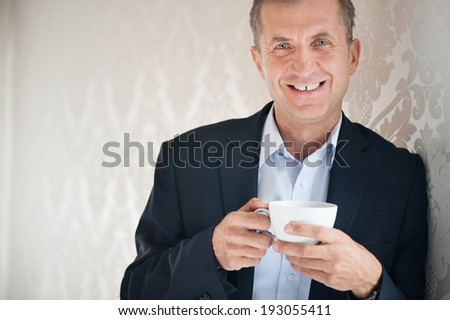 Handsome man holding cup of coffee in suit - stock photo