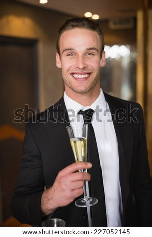 Handsome man holding flute of champagne at the bar - stock photo