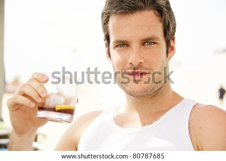 Handsome man holding glass - stock photo