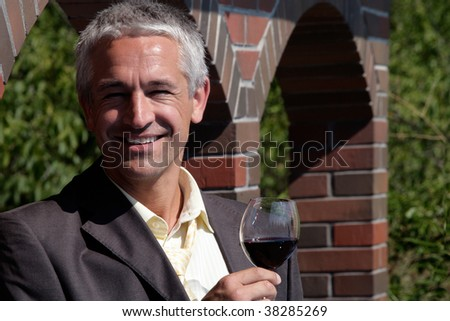 Handsome man holding glass of red wine - stock photo