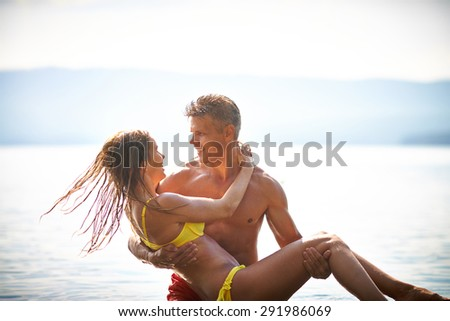 Handsome man holding happy woman in bikini while standing in water - stock photo