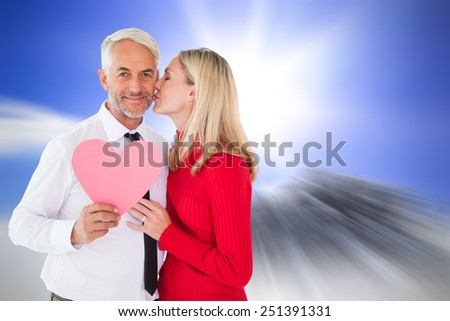 Handsome man holding paper heart getting a kiss from wife against large rock overlooking bright sky - stock photo