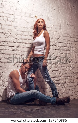 Handsome man hugging his girlfriend leg. While sitting on the flour  - stock photo