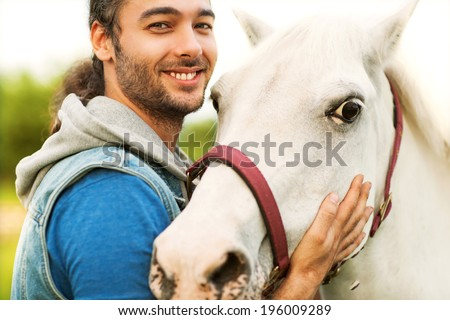 Handsome man in a black coat riding on a brown horse  - stock photo