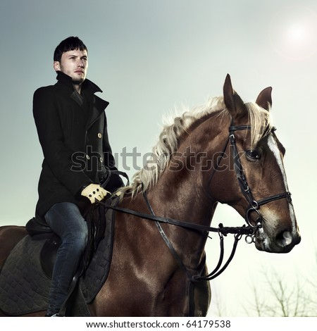 Handsome man in a black coat riding on a brown horse