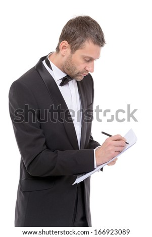 Handsome man in a bow tie and elegant suit standing writing notes, isolated on white