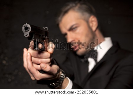 handsome man in a suit aim with a gun  - stock photo