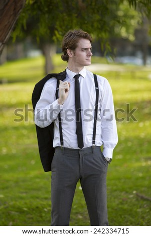 handsome man in a suit standing in a park - stock photo