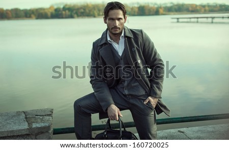 Handsome man in autumn scenery - stock photo
