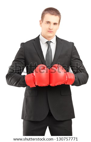 Handsome man in black suit with red boxing gloves posing isolated on white background - stock photo
