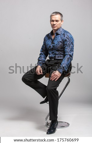 Handsome man in blue shirt sitting on high chair against white background - stock photo