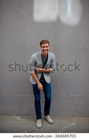 Handsome man in blue shirt standing near the wall and smiling - stock photo