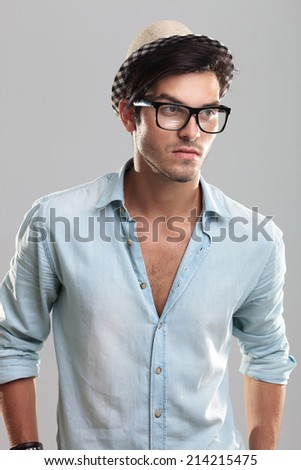 Handsome man in blue shirt, wearing glasses, on gray background - stock photo