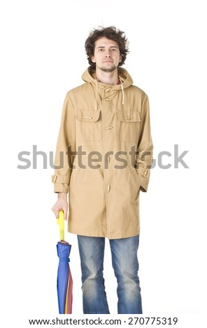 Handsome man in brown vintage raincoat holding colorful umbrella. - stock photo