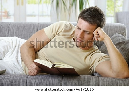 Handsome man in causal wear smiling lying on sofa reading handheld book. - stock photo