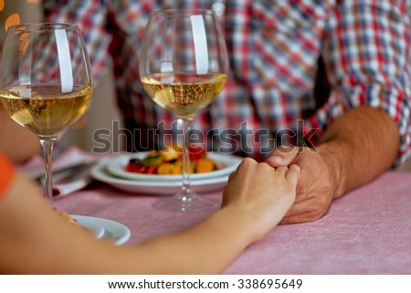 Handsome man in checked shirt holds woman's hand in the restaurant