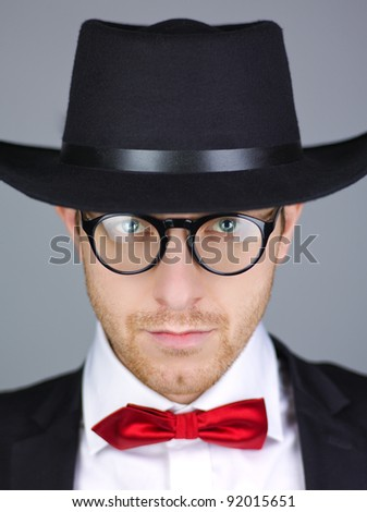 Handsome man in formal black jacket with red bow tie and hat, studio background.