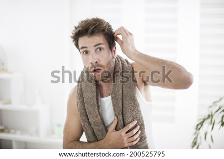 handsome man in his bathroom examines his face - stock photo