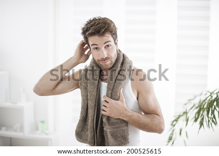 handsome man in his bathroom examines his hair - stock photo