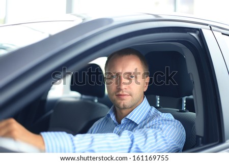 Handsome man in his new car - stock photo