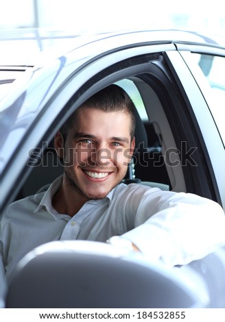 Handsome man in his new car and smiling at camera   - stock photo