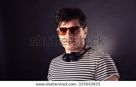 Handsome man in his 40's wearing bluetooth headphones and sunglasses, dressed in a striped T shirt. Studio shot with grey background, slightly toned. - stock photo
