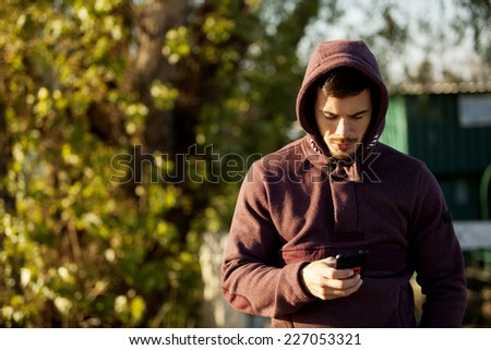 Handsome Man In Hoodie Holding Mobile Smart Phone Outdoor - stock photo