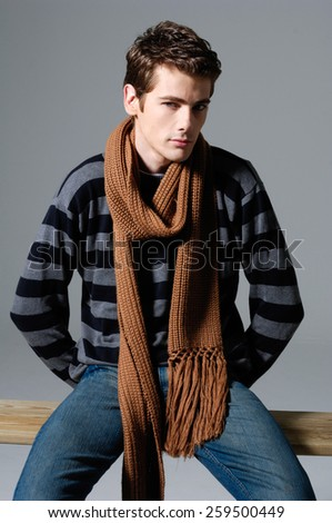 Handsome man in jeans sitting chair over a grey background - stock photo